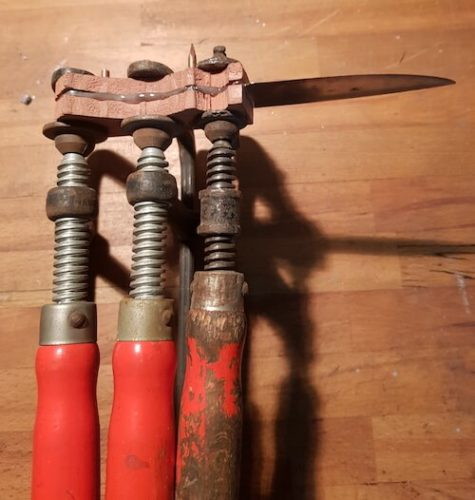 Messer und Holzgriff in Schraubzwinge eingespannt